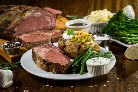 Prime rib maaltijd geserveerd op een tafel met ingrediënten rondom het hoofdgerecht Stockfoto