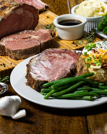 prime rib meal served on a table with ingredients surrounding the main dish