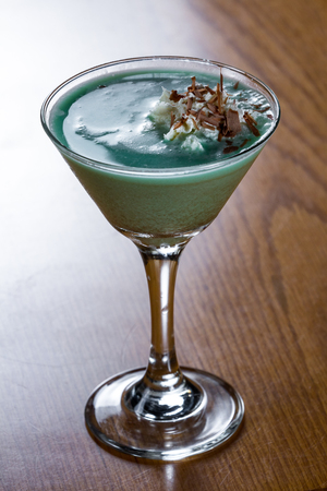 close up of a classic grasshopper cocktail served in a martini glass with a dollop of whipped cream with chocolate shavings