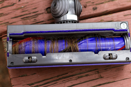 Close up of the under side of a vacuum cleaner with hair wrapped around the brushes Stock Photo