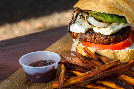 grilled plant based burger served with a home made sauce sweet potato fries on a wooden cutting board Stockfoto