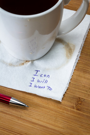 hand written note on a coffee stained napkin with an empowering message, I can I will I want to.