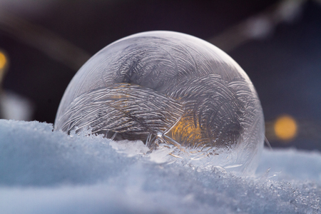 Close up of a small soap bubble freezing rapidly due to extreme cold temperatures in winter Reklamní fotografie