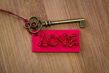 conceptual image using an old key with a red tag with glitter letters spelling the word love over a wooden background