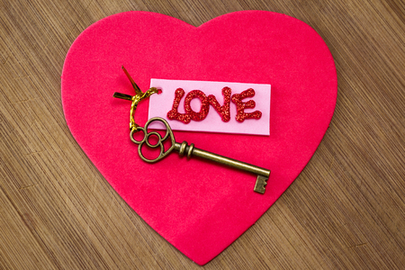 conceptual image using an old key with a pink tag with red glitter letters spelling the word love Stockfoto