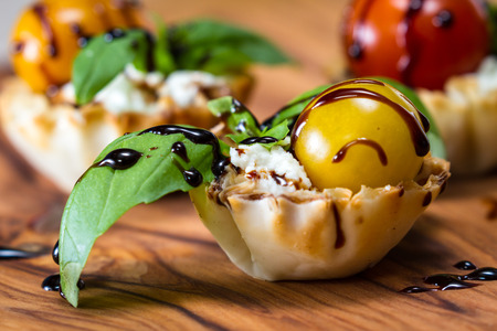 delicious puff pastry cups filled and baked with goat cheese topped with fresh basil and tomato with a balsamic drizzle