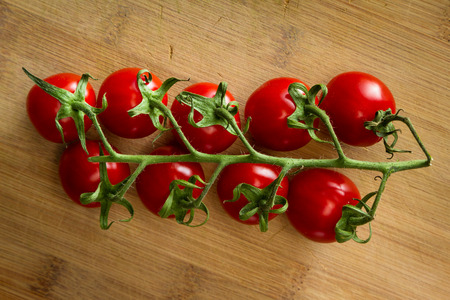 close up of a group of vine ripened strawberry tomatoes with a vibrant red color
