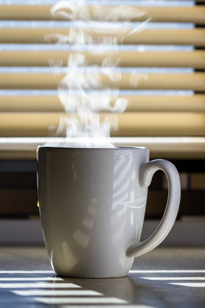 Close up of a fresh steaming cup of coffee served indoors with blinds allowing enough light to light up the steam and countertop Banco de Imagens