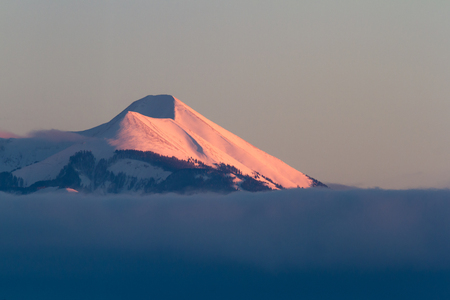 Close up of one of the La Sal Mountains at sunset with a pink glow reflecting on the snow