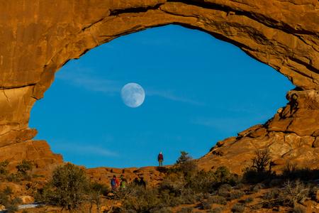 Belle vue sur la pleine lune se levant par la fenêtre nord dans le parc national des Arches