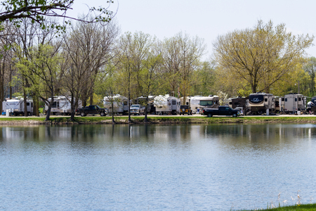Sycamore, Illinois - May 07: Recreational vehicles parked at the waters edge with a peaceful reflection on the tranquil pond at the Sycamore RV Park. May 07, Sycamore, Illinois. Éditoriale