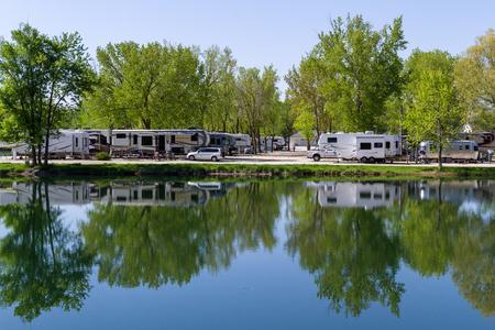 Sycamore, Illinois - 16 mai : Véhicules récréatifs garés au bord de l'eau avec une réflexion paisible sur l'étang tranquille du Sycamore RV Park. 16 mai, Sycomore, Illinois.