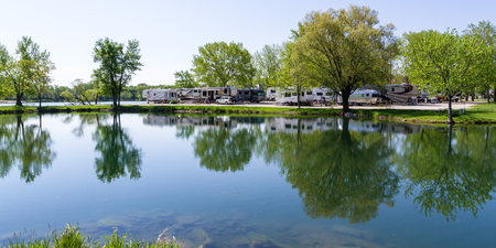 Sycamore, Illinois - May 16: Recreational vehicles parked at the waters edge with a peaceful reflection on the tranquil pond at the Sycamore RV Park. May 16, Sycamore, Illinois. Éditoriale