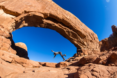 man pretending to trip and fall as a concept to be be careful while hiking on the slick red rocks
