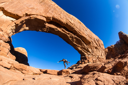 man pretending to trip and fall as a concept to be be careful while hiking on the slick red rocks 스톡 콘텐츠 - 119433555