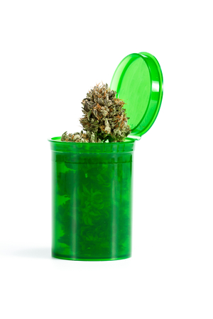Close up of a green prescription bottle with cannabis buds isolated on a white background