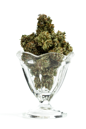 Close up of an old style decorative glass serving dish loaded with cannabis buds isolated on a white background Stock Photo