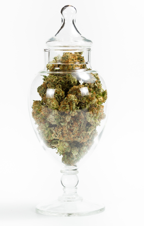beautiful glass storage container filled with marijuana buds isolated on a white background Banco de Imagens