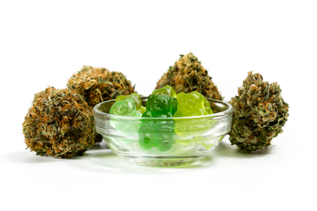 clear bowl filled with gummy bears and marijuana buds around isolated on a white background