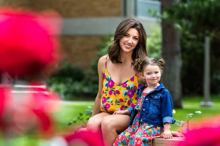 young mother and her daughter sitting on a bench near a rose garden in Coeur d Alene Idaho