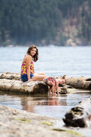 young mother and daughter enjoying summer in Coeur d Alene Idaho spending time by the water