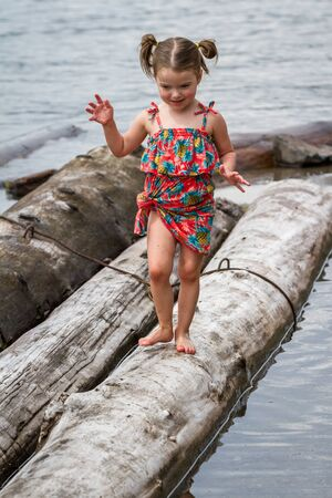 cute young girl playing by the logs in Coeur d Alene lake Idaho