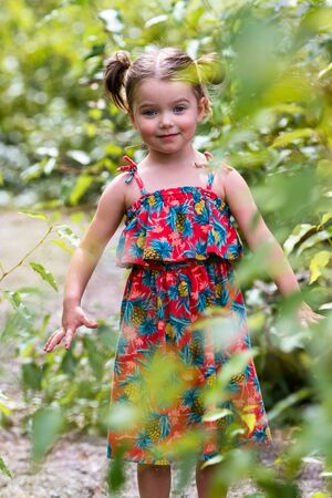 young adorable girl posing outdoors with green leaves for an outdoor photo session