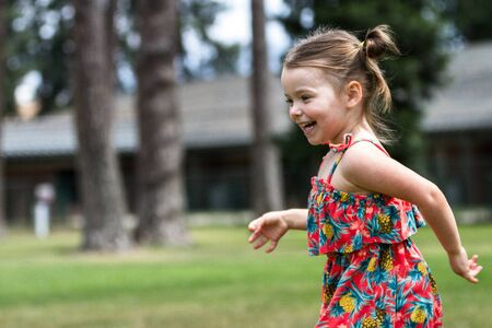 care free child smiling and running in circles with green grass and trees in Coeur d Alene Idaho Фото со стока