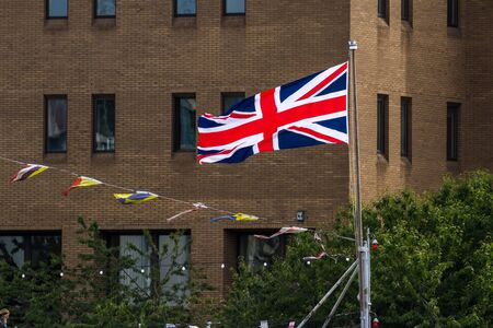 Close up of the Union Jack Flag in London with old brick buildings in the Background