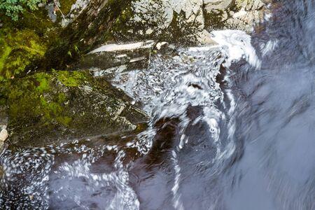 Aguas marrones que corren en las Tierras Altas de Escocia como producto de la turba en las Tierras Altas Foto de archivo