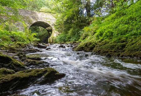 Banvie Bridge near Pitlochry in the Scottish Highlands as the fresh water water runs downstream over the moss covered rocks