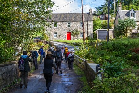Pitlochry Scotland  - September 10 2019: Group of people walking by the old Post Office identified by the red door, UK September 10,  2019