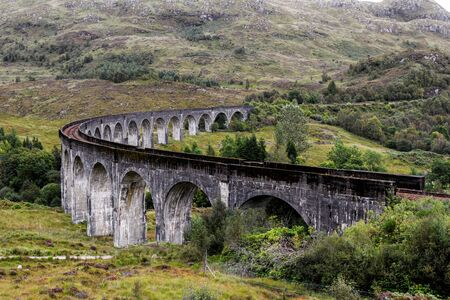 Beautiful iconic scene in the Scottish Highlands with the Glenfinnan Viaduct and the green classic landscape.