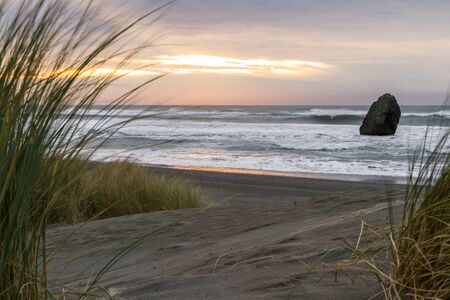 Beautiful scene as the sun sets on the horizon adding color to the dark clouds and a bit of light to the sand and grasses found in the Oregon coast.