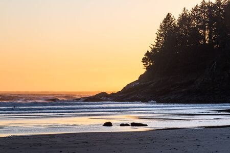 Man in the cold coastal waters of the Oregon coast surfing at sundown with an orange glow on the horizon