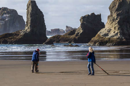 Bandon by the Sea, Oregon / USA - February 21 2020: Denny Dike and the team of Circles in the Sand drawing a walkable labyrinth in the flat sandy beach of Face Rock State Park
