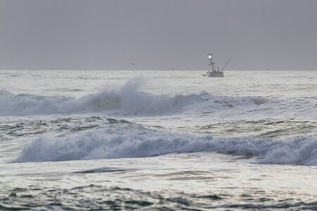Fishing charter in the Oregon coast with rough seas as the day comes to and end with a thick fog bank in the background and cloudy grey skies