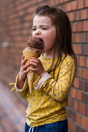 Close up of an adorable little girl eating a large chocolate ice cream cone with a brick wall in the background
