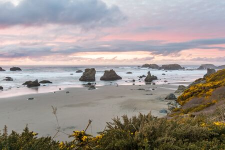 end of the day at the beach a bit of color in the dark clouds and the prominent rock features characteristic Face Rock State Park, Bandon Oregon 写真素材