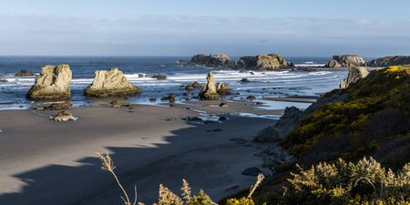 Beautiful morning in Face Rock State Park, Bandon Oregon with the sunlight catching the waves adding highlights to the scene 写真素材