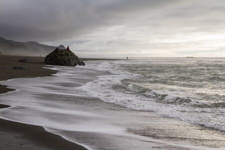 unrecognizable persons enjoying a dull and dramatic day in the southern Oregon coast 写真素材