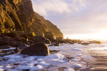 Golden light reflecting on the rocks at Cape Sebastian as the sun drops below the horizon adding brightness and color to the scenic landscape in the southern Oregon coast