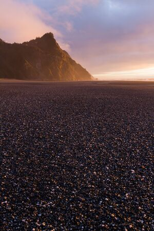 Gorgeous soft and colorful light from the setting sun adding drama and beauty to the end of the day beach scene with Cape Sebastian at the distance in the southern Oregon coast