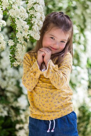 portrait of a happy four year old little girl with white blooming flowers 写真素材