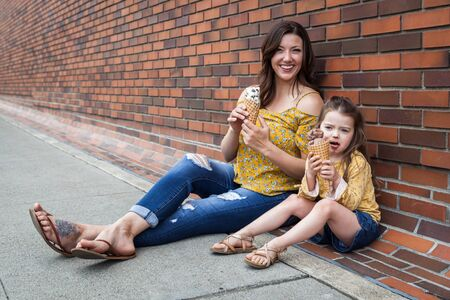 Mom and daughter eating ice cream outdoors with a brick wall in the background 写真素材