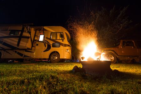 glowing flames and sparks flying our of a fire ring with a large recreational vehicle in the background as a camping concept