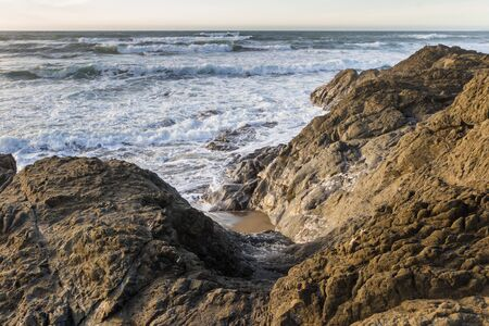 Rocky shoreline in Nesika Beach, Oregon late in the afternoon with the sun approaching the horizon and the waves moving with the changing tides 写真素材