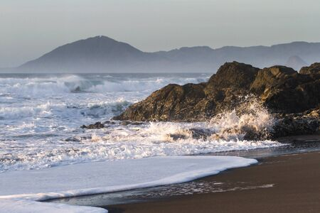 Rocky shoreline in Nesika Beach, Oregon late in the afternoon with the sun approaching the horizon and the waves crashing into the rocks 写真素材