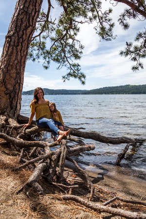 Mother and daughter with matching outfits sitting on the exposed roots of a tree in lake Coeur d' Alene in northern Idaho