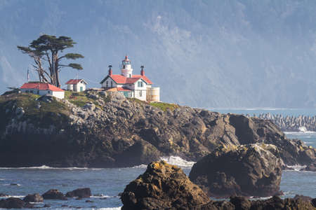 Tidal island just offshore Crescent City California home to one of the most visited structures in Del Norte County , Battery Point Lighthouse seen here at low tide with a bit of mist in the air against the dark mountains in the background.